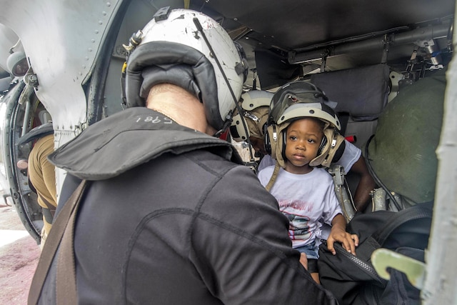 A child wearing a helmet inside a helicopter looks at a sailor.