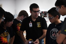 Capt. Victor, 17th Attack Squadron MQ-9 Reaper pilot, shows a high school robotics team how to work with an electric drill, in Las Vegas, Sept. 7, 2017.