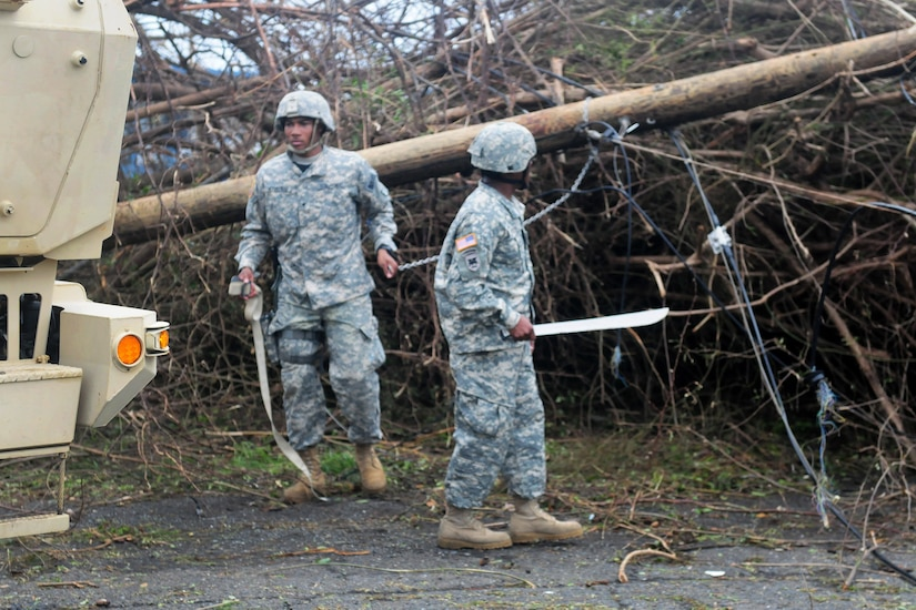 Guardsmen clear debris and downed power lines from the Melvin Evans highway in St. Croix.