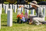 A woman kneels to place an object on top of a grave stone that has an American flag and flowers next to it.