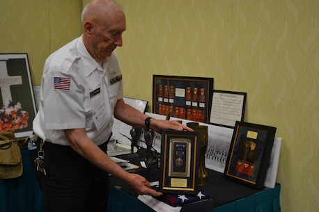 Navy Capt. retired Lee S. Anthony, an 80th Division Veterans Association member and son of Pvt. Lee Hill Anthony, a 80th Training Division World War I veteran, shows the Purple Heart his father earned while serving during WWI. His father was injured April 4, 1918. (U.S. Army photo by Sgt. 1st Class Emily D. Anderson, 80th Training Command)