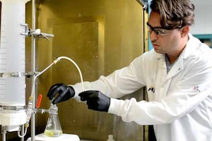 A scientist pours powder into a beaker of urine.