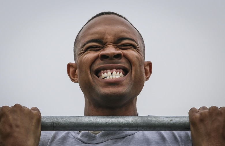 Staff Sgt. Garion Reddick fights to hold himself up during the flex arm hang portion of a German Armed Forces Badge for Military Proficiency test at Joint Base McGuire-Dix-Lakehurst, N.J., Sept. 17, 2017. Reddick is assigned to the 108th Maintenance Squadron. (U.S. Air National Guard photo by Master Sgt. Matt Hecht)