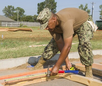 Navy Command Master Chief Delbert Terrell Jr. measures a window frame during a community outreach project.