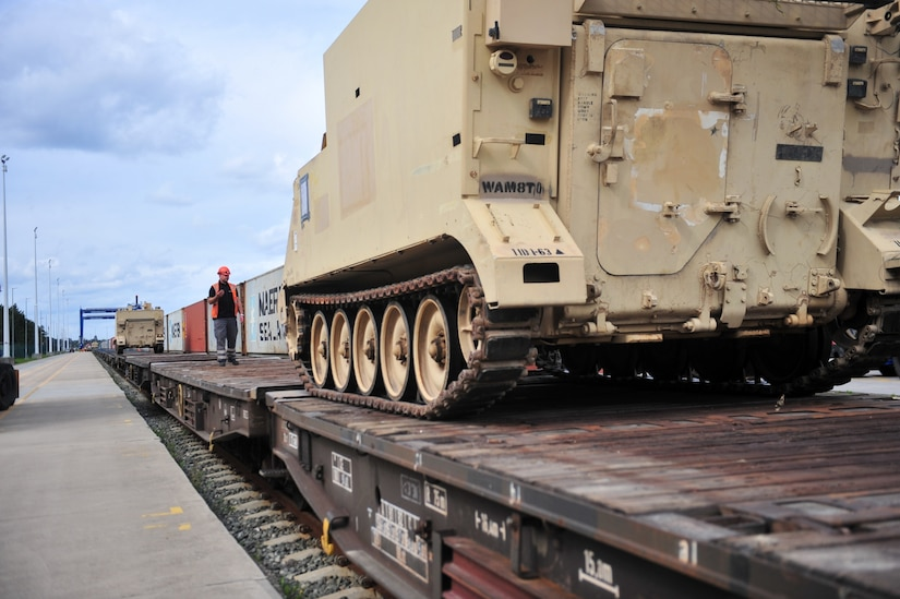 M577 Armored Command Vehicles are driven on to train cars at the port of Gdansk, Poland.
