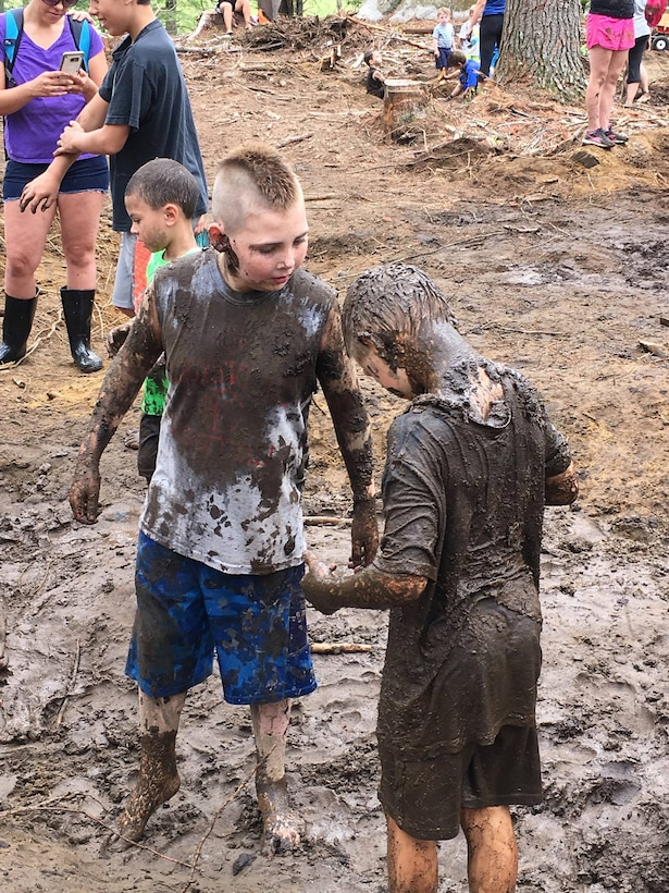 Two boys playing in mud.