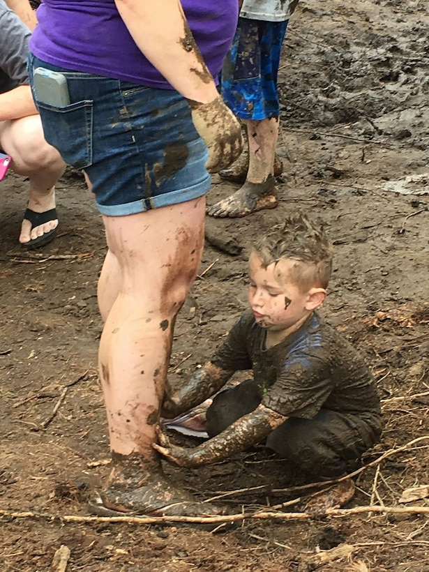Boy smearing mud on his parent.