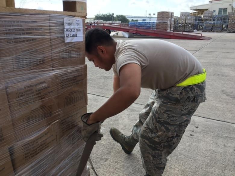 Airman 1st Class Mavin Raboy, 26th Aerial Port Squadron straps down cargo pallets Sept. 22, 2017 at Joint Base San Antonio-Kelly Field.  The supplies were being staged at the Federal Emergency Management Agency's Incident Support Base at Kelly for transport to areas devastated by Hurricane Maria (U.S. Air Force image/Dan Hawkins)