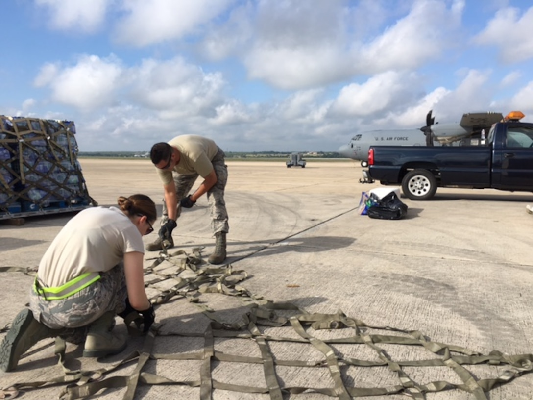 Senior Airman Sarah Nededog (fore) and Tech. Sgt. Antonio Montano, 502nd Logistics Readiness Squadron traffic management office, straighten out cargo straps to help prepare Hurricane Maria relief supplies for air transport Sept. 22, 2017 at Joint Base San Antonio-Kelly Field.  The supplies were being staged at the Federal Emergency Management Agency's Incident Support Base at Kelly for transport to areas devastated by Hurricane Maria (U.S. Air Force image/Dan Hawkins)