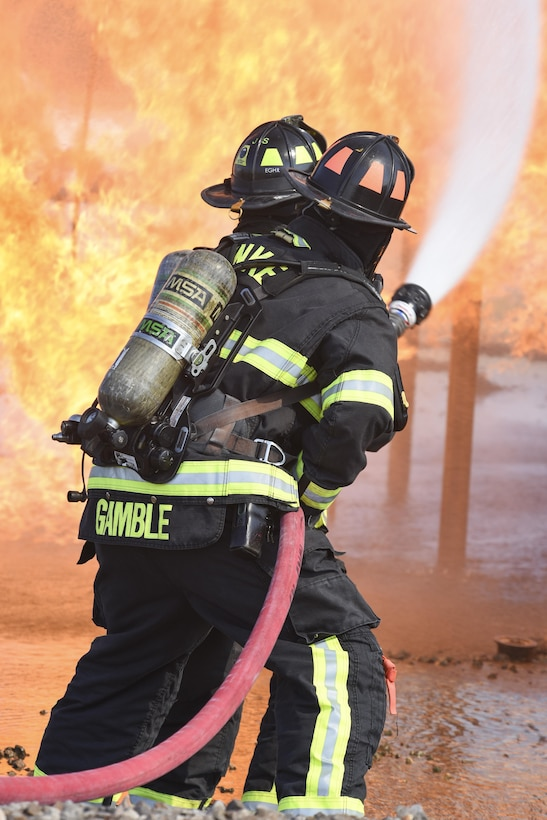 Two member teams from the 72nd Civil Engineer Squadron, fire department, work together as they approach the full-size aircraft fire training device Sept. 13, 2017, Tinker Air Force Base, Oklahoma. The firefighters were conducting annual  recertification training in the realistic environment.