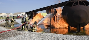 Members of the Tulsa Fire Department (wearing tan bunker gear) work with a member of the 72nd Civil Engineer Squadron, fire department, during a training event using a full-size aircraft fire training device Sept. 13, 2017, Tinker Air Force Base, Oklahoma. The Tulsa firefighters were guests of the 72nd Civil Engineer Squadron, fire department, who underwent recertification training.