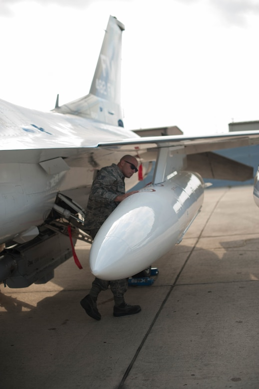Staff Sgt. Joel Folguiera performs inspections on an F-16 after it relocated to Naval Air Station Fort Worth Joint Reserve Base, Texas, in order to stay out of harm's way during Hurricane Irma.