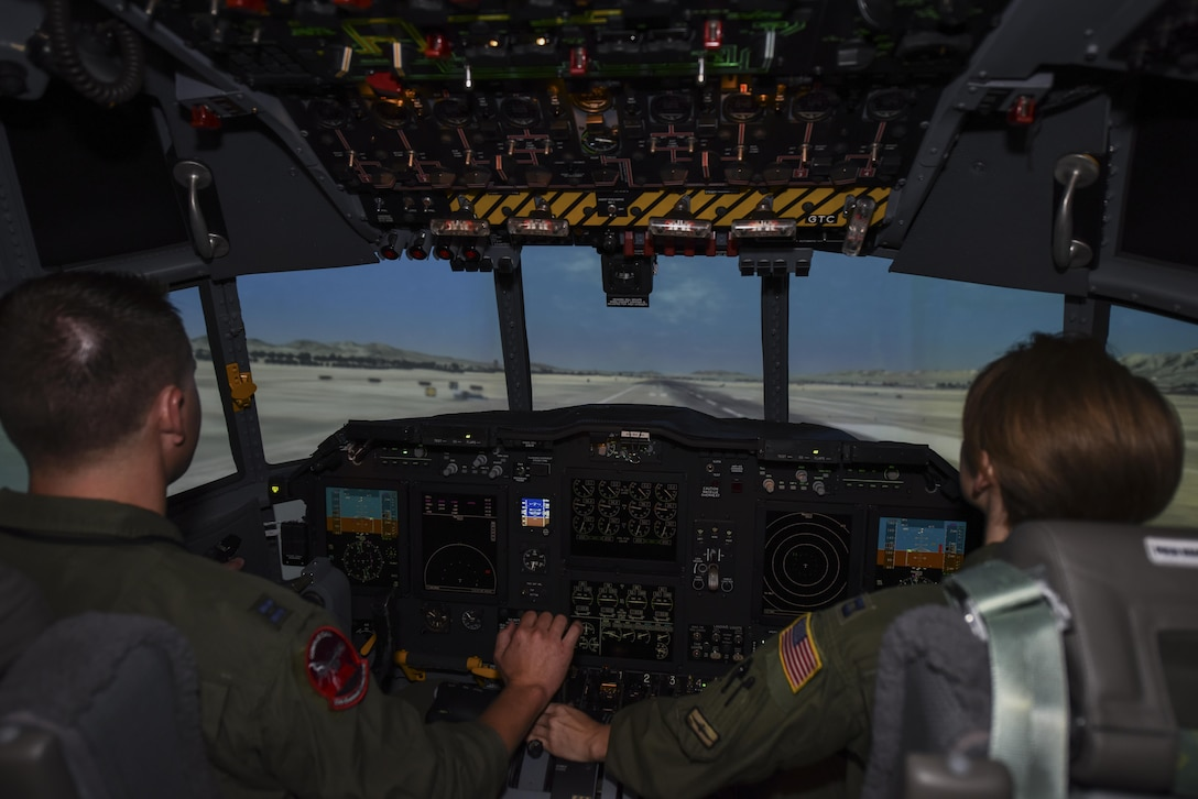 U.S. Air Force Capt. Brett Neilson, 55th Electronic Combat Group instructor, and Capt. Megan Russell, 42nd Electronic Combat Squadron evaluation pilot, simulate a landing of an EC-130H Compass Call at Davis-Monthan Air Force Base, Ariz., Sept. 22, 2017. The 42nd ECS flight simulator went through a $10.5 million upgrade to better prepare the pilots for their future flights.