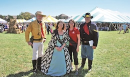 A reenactor dressed as Lt. Col. George Armstrong Custer, left, stands with the 2016 Pie Queens Jane MacDougall, second from the left, wife of Col. Mark MacDougall, chief of nursing officer at Irwin Army Community Hospital, and Lauren Bolen, second from the right, wife of Col. Thomas Bolen, commander of 1st Infantry Division Artillery, and a reenactor acting as Custer's aide, right, Sept. 10, 2016, at Fall Apple Day.