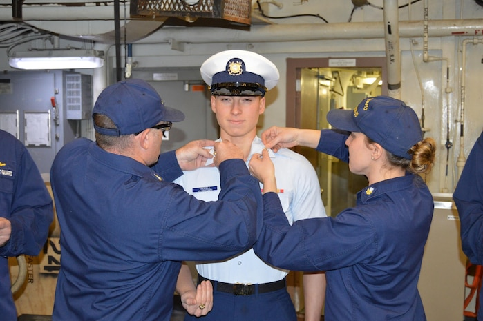 CSCS Wheeler and CS1 Densmore pin on CS3 Trudell's new rank insigna following his advancement.