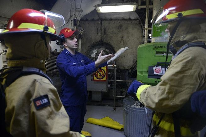 LT O'brien instructs SA Baker-Rodriguez and BM3 Shoopman on proper firefighting techniques during emergency response drills.