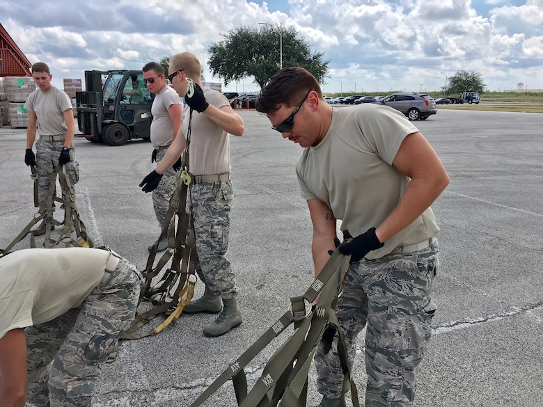 Second Lt. Alberto, 12th Training Squadron student, straightens out cargo straps to help prepare Hurricane Maria relief supplies for air transport Sept. 22, 2017, at Joint Base San Antonio-Kelly Field.  The supplies were being staged at the Federal Emergency Management Agency's Incident Support Base at Kelly for transport to areas devastated by Hurricane Maria. (U.S. Air Force image/Dan Hawkins)