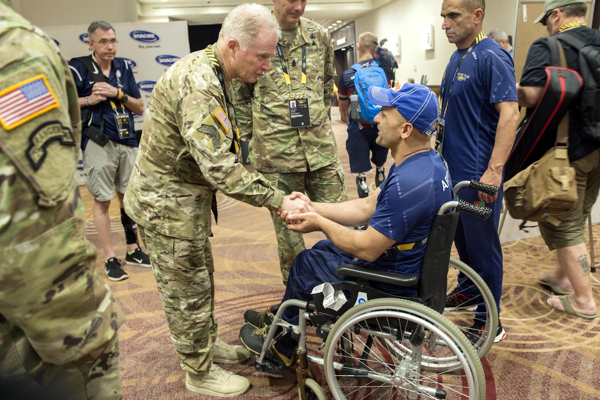 An army general leans over to shake the hand of a person in a wheelchair.