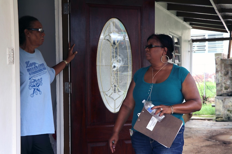 Department of Planning and Natural Resources Office Manager for Business and Administration Services talks to a home owner, helping Operation Blue Roof team members as they walk house-to-house. With five team members on the island, the Temporary Roofing Planning and Response Team is currently going house-to-house gathering Right of Entry forms. The forms allow Corps personnel on private property to assess homes and Corps contractors authority to repair the roofs. More Temporary Roofing team members are on their way. Operation Blue Roof's purpose is to provide homeowners in disaster areas with fiber-reinforced plastic sheeting to cover their damaged roofs until arrangements can be made for permanent repairs.