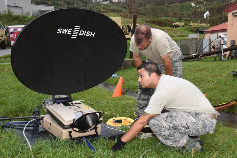 Chief Master Sgt. Don Johnnson and Staff Sgt. Tony Baca, Joint Incident Site Communication Capability team members with the 151st Air Refueling Wing Communications Flight in Salt Lake City, Utah, set up a SWE-DISH CCT120 satellite dish outside the Leonard B. Francis Armory in St. Thomas, U.S. Virgin Islands, Sept. 20, 2017. The Sept. 7 deployment of the Utah JISCC helped re-establish critical military and emergency civil service communications within areas of the U.S. Virgin Islands severely impacted by Hurricanes Irma and Maria.  (U.S. Air National Guard photo by Master Sgt. Paul Gorman)