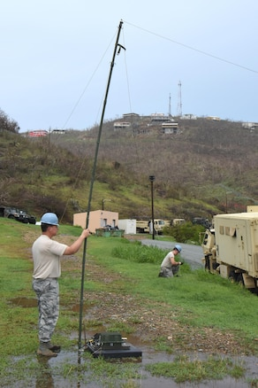 Master Sgt. David Fernelius, left, and Airman 1st Class David Zham, Joint Incident Site Communication Capability team members with the 151st Air Refueling Wing Communications Flight in Salt Lake City, Utah, erect an NVIS high frequency antenna outside the Leonard B. Francis Armory in St. Thomas, U.S. Virgin Islands, Sept. 20, 2017. The Sept. 7 deployment of the Utah JISCC helped re-establish critical military and emergency civil service communications within areas of the U.S. Virgin Islands severely impacted by Hurricanes Irma and Maria. (U.S. Air National Guard photo by Master Sgt. Paul Gorman)