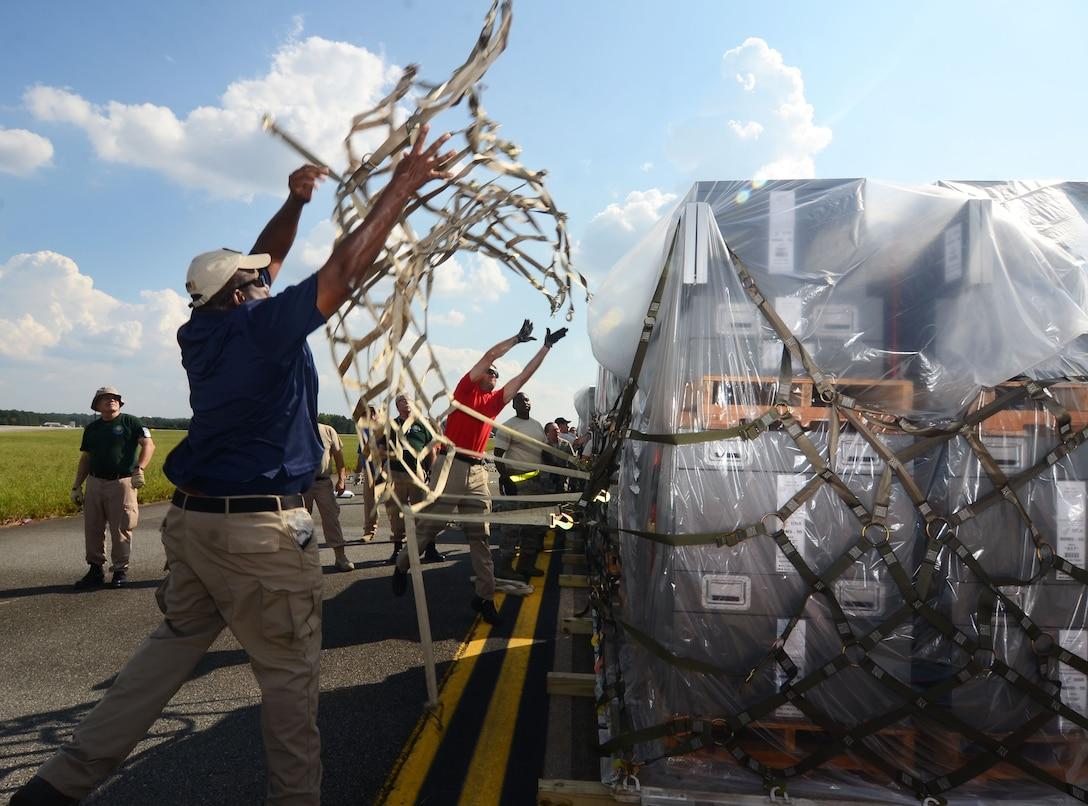 Department of Health and Human Services logistician throws a cargo net over a pallet on the flightline at Dobbins Air Reserve Base, Ga. Sept. 21, 2017. This cargo included items needed to build a hospital from scratch – everything from the tents required to house the temporary structure to the medical equipment used to treat patients. (U.S. Air Force photo/Don Peek)