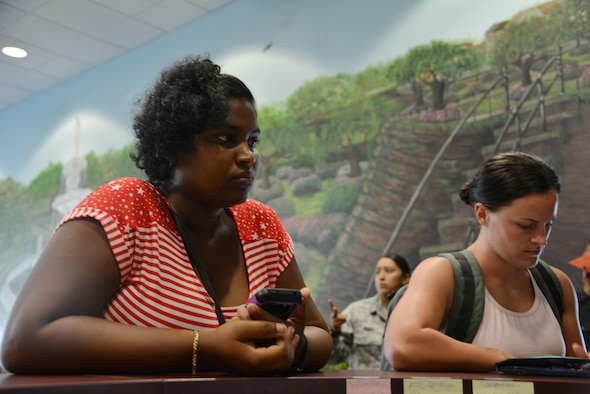 Shantel Rogers, a military spouse who evacuated from St. Croix, Virgin Islands, awaits a lodging assignment at the Savannah Air National Guard Base, Sept. 24, 2017. The USO reception area provides food, toiletries and lodging assignments for service members supporting hurricane relief efforts and their families. (U.S. Air National Guard photo/Staff Sgt. Chelsea Smith)