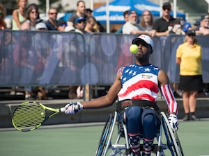 Roosevelt Anderson prepares to return a serve during a wheelchair tennis match.