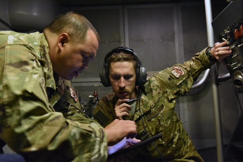Capt. Joe, right, assists boom operator Tech. Sgt. Fritz in trouble shooting an issue in a KC-10 Extender boom pod in the air over Syria, Sept. 13, 2017.