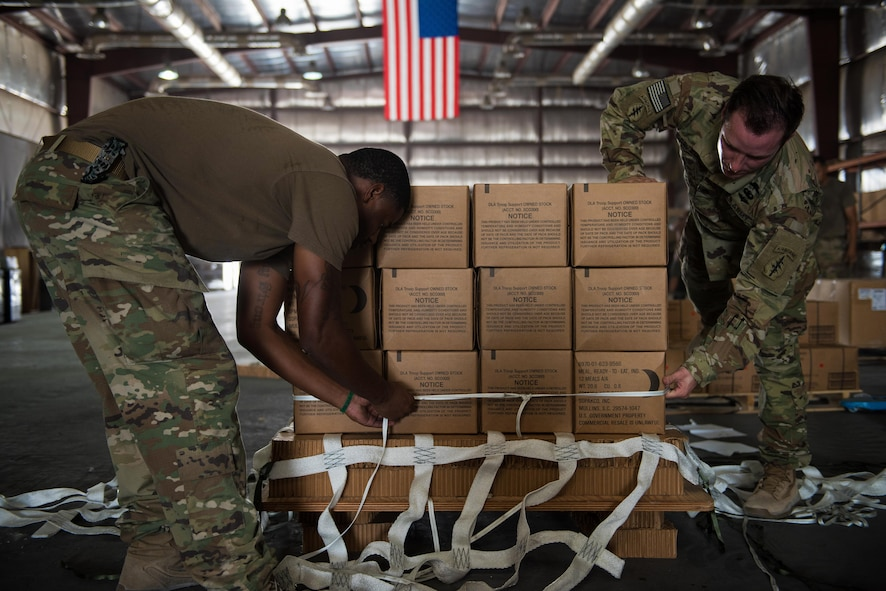 U.S. Army Sgt. Timothy Williams, a parachute rigger assigned to the 824th Quartermaster Company, and U.S. Army Staff Sgt. Justin Devaul, a parachute rigger assigned to an Army special operations forces unit, work together to build an airdrop bundle of meals, ready-to-eat for forward deployed troops at an undisclosed location in Southwest Asia, Sept. 6, 2017. Airdrop bundles are rigged within specific guidelines to ensure the cargo properly exits the aircraft, the parachute properly deploys and the bundle lands intact on its target. (U.S. Air Force photo by Tech. Sgt. Jonathan Hehnly)
