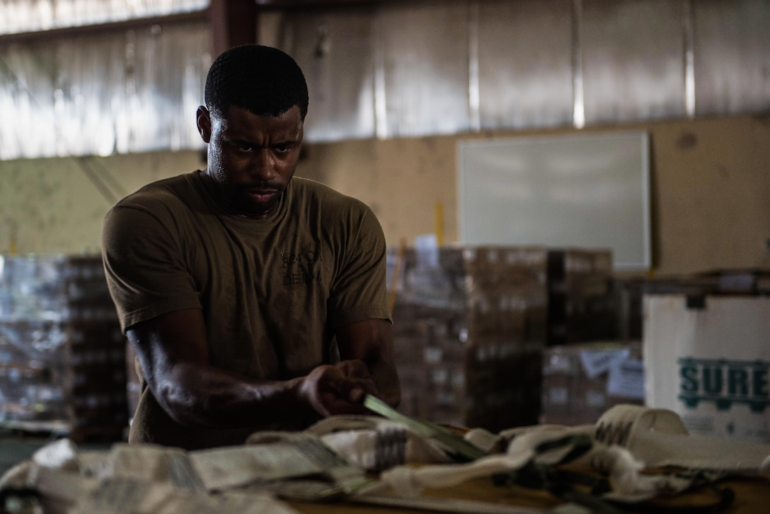 U.S. Army Sgt. Timothy Williams, a parachute rigger assigned to the 824th Quartermaster Company, pulls a strap to tighten an airdrop bundle at an undisclosed location in Southwest Asia, Sept. 6, 2017. Airdrop bundles are rigged within specific guidelines to ensure the cargo properly exits the aircraft, the parachute properly deploys and the bundle lands intact on its target. (U.S. Air Force photo by Tech. Sgt. Jonathan Hehnly)