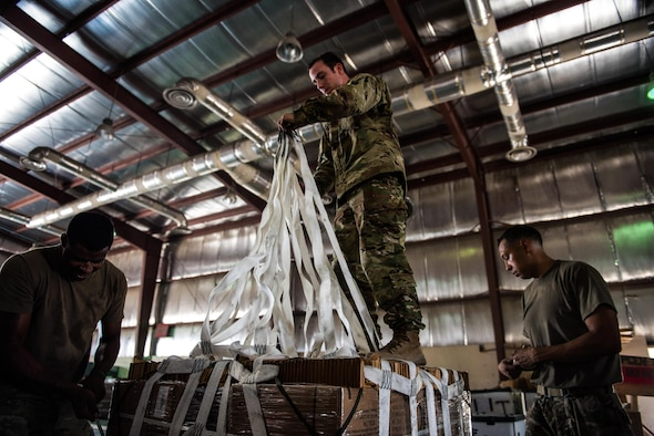 A team of U.S. Army parachute riggers rig a supply bundle in preparation for an airdrop