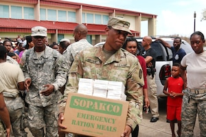 A soldier carries a box of supplies.