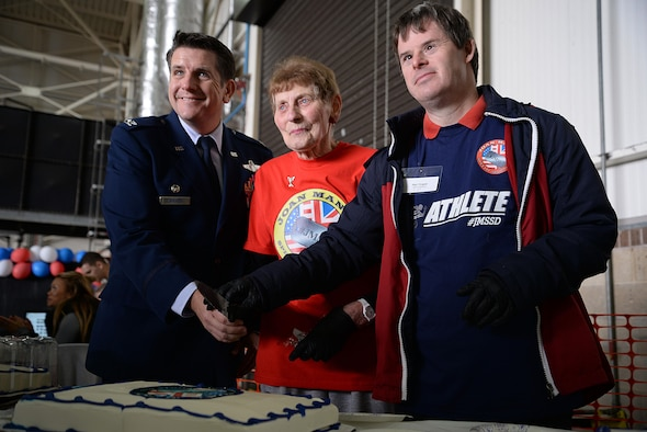 "U.S. Air Force Col. Christopher Amrhein, 100th Air Refueling Wing commander, volunteer Iris Weimer, volunteerand Neil Draper, perform the cake cutting ceremony for the 36th Annual Joan Mann Special Sports Day, Sept. 23, 2017, on RAF Mildenhall, England. The event opened with the lighting of the Olympic torch and the ""Parade of Athletes,"" followed by the sporting events, and concluded with medal presentations. (U.S. Air Force photo by Senior Airman Christine Groening)"