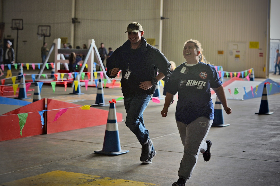 An athlete and her escort race against one another during 100-yard race at the Joan Mann Special Sports Day, Sept. 23, 2017, on RAF Mildenhall, England. The event included an obstacle course, basketball shoot-out, ball toss and other competitions for the athletes. (U.S. Air Force photo by Senior Airman Christine Groening)