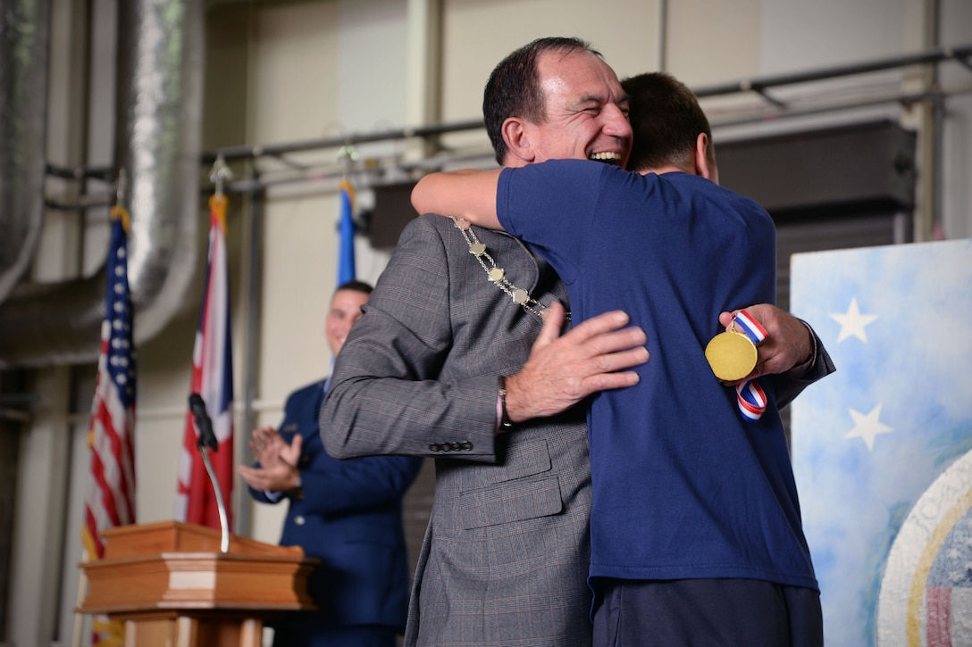 Councilor Terry Clements, Mayor of Edmundsbury, embraces one of the winning athletes during the awards ceremony for Joan Mann Specials Sports Day, Sept. 23, 2017, at RAF Mildenhall, England. The event was established 36 years ago when Joan Mann, a Ministry of Defence employee on RAF Mildenhall, wanted to find a way to bring the local community and military members together to work with special-needs citizens.  (U.S. Air Force photo by Senior Airman Christine Groening)