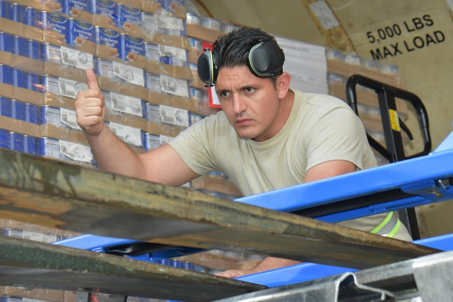 Air National Guard Staff Sgt. Jesus Rosales, air transportation specialist with the 161st Air Refueling Wing in Phoenix, Arizona directs a forklift operator during the download of food pallets at Cyril E. King Airport in St. Thomas, U.S. Virgin Islands Sept. 15, 2017. 161st ARW personnel joined Airmen assigned to the 133rd Airlift Wing in Minneapolis, Minnesota, and 146th Airlift Wing in Camarillo, California to manage air operations at the storm damaged airport in St. Thomas in the wake of Hurricane Irma. (U.S. Air National Guard photo by Master Sgt. Paul Gorman)