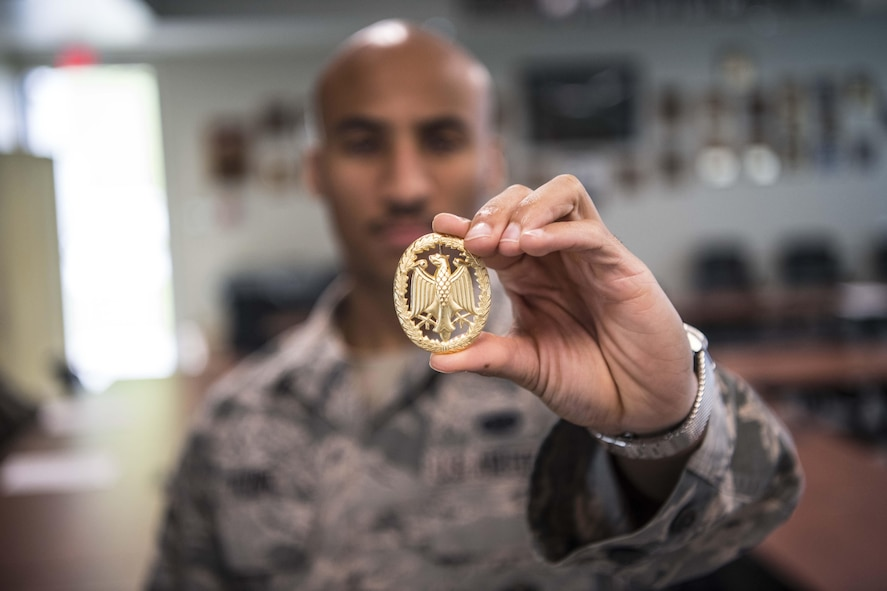 Staff Sgt. Johnathan Flynn, a defender with the 130th Airlift Wing, holds the gold German Armed Forces Proficiency Badge (GAFPB), Sept. 16, 2017, at McLaughlin Air National Guard Base, Charleston, West Virginia. The GAFPB a decoration of the Bundeswehr, the Armed Forces of the Federal Republic of Germany. As one of the few foreign badges that are authorized to be worn on the U.S. military uniform, the GAFPB is one of the most highly sought-after awards. Flynn earned the gold badge after completing a rigorous course with nine other defenders from the 130th AW. (U.S. Air National Guard photo by Tech. Sgt. De-Juan Haley)