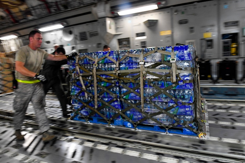 Airmen unload a pallet of water from a Joint Base Charleston C-17 Globemaster III in St. Croix, Virgin Islands, Sept. 24, 2017. Members of the 14th Airlift Squadron, 437th Airlift Wing, delivered more than 129,000 pounds of food and water to St. Croix in support of relief efforts after Hurricane Maria. The mission to St. Croix marked the second mission the crew flew to the Virgin Islands for humanitarian aid in 48 hours.