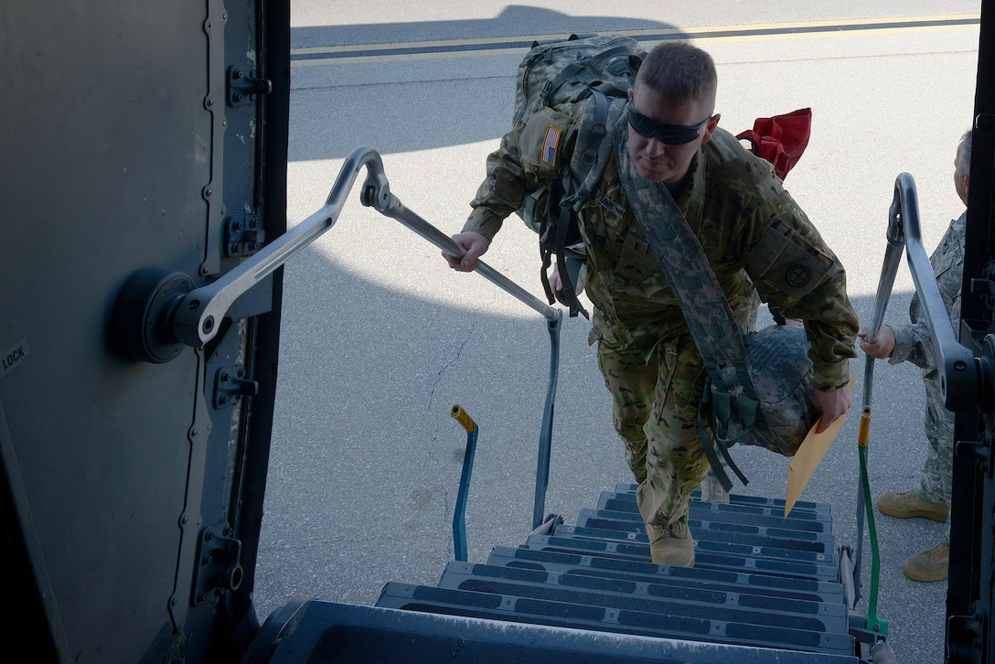 A soldier climbs the stairs into an aircraft.