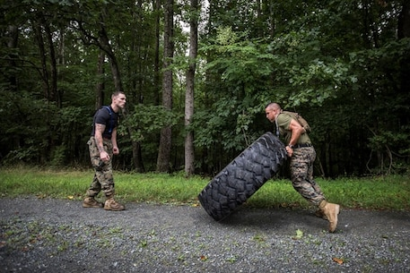 FFIT Sgt. Cody Anderson monitors form and motivates a Marine executed a tire flip during a Physical Training session as part of Force Fitness Instructor Course 4-17.