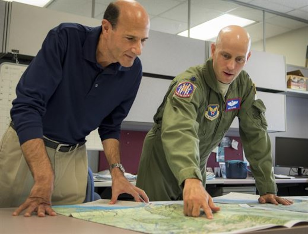 Lt. Col. Robert Clark, AFOTEC Detachment 2 Air Armament Division chief, and Paul LaPorta, unit test director, compare legacy navigation charts from the 1960s with newly updated digitized versions. The detachment recently evaluated new, fully digitized navigation charts that will streamline mission planning initiatives for the military as early as 2019. (U.S. Air Force Photo/Jasmine Porterfield)