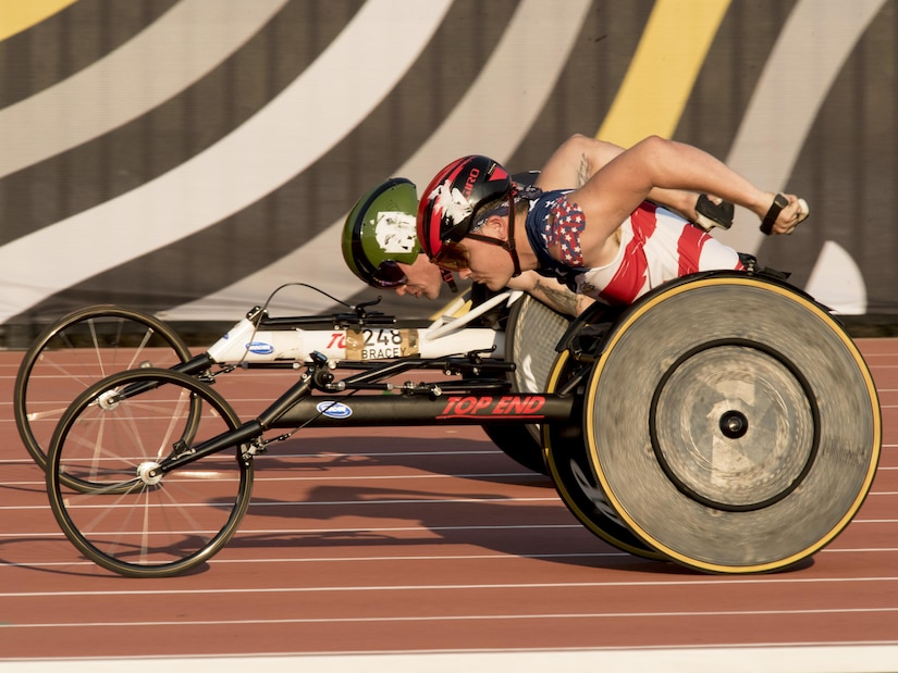 A Team U.S. member passes a Team Great Britain member in a wheelchair race.