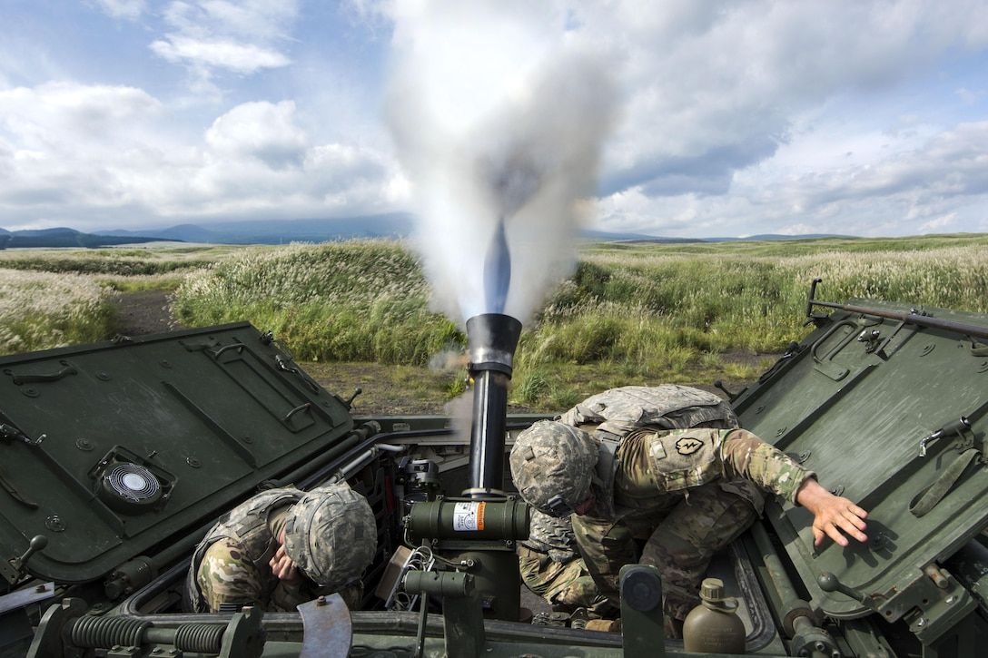 Soldiers crouch as a mortar system fires.