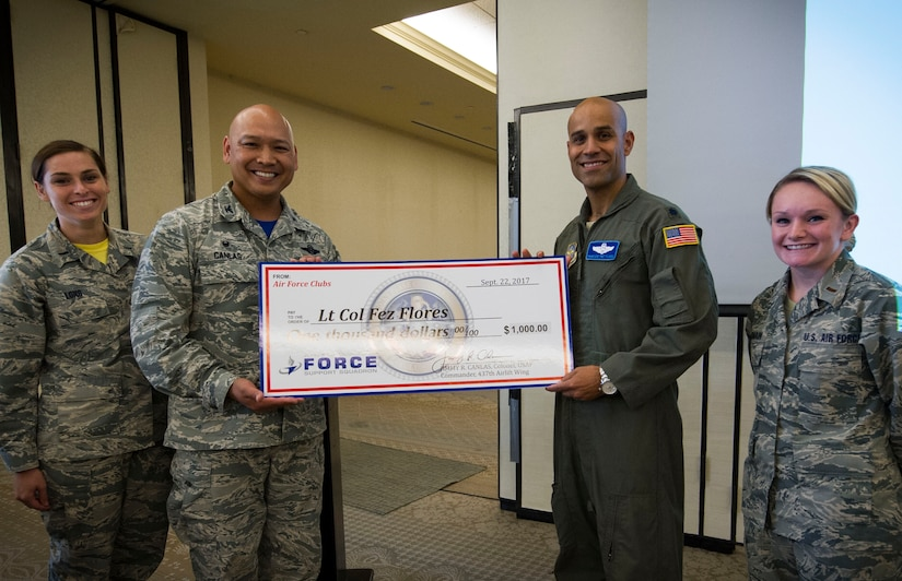 Col. Jimmy Canlas, 437th Maintenance Group commander, left, presents a check to Lt. Col. Francisco Flores, 437th Operations Support Squadron director of operations, right, during the U.S. Air Force's 70th Anniversary celebration at the Charleston Club, Sept. 22, 2017.