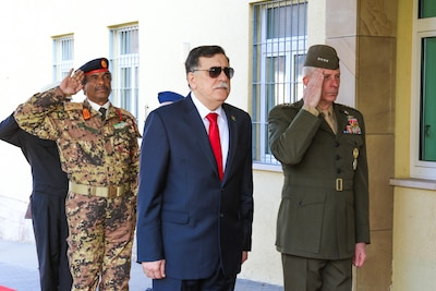 Libyan prime minister and U.S. Africom commander render honors at ceremony before a meeting.