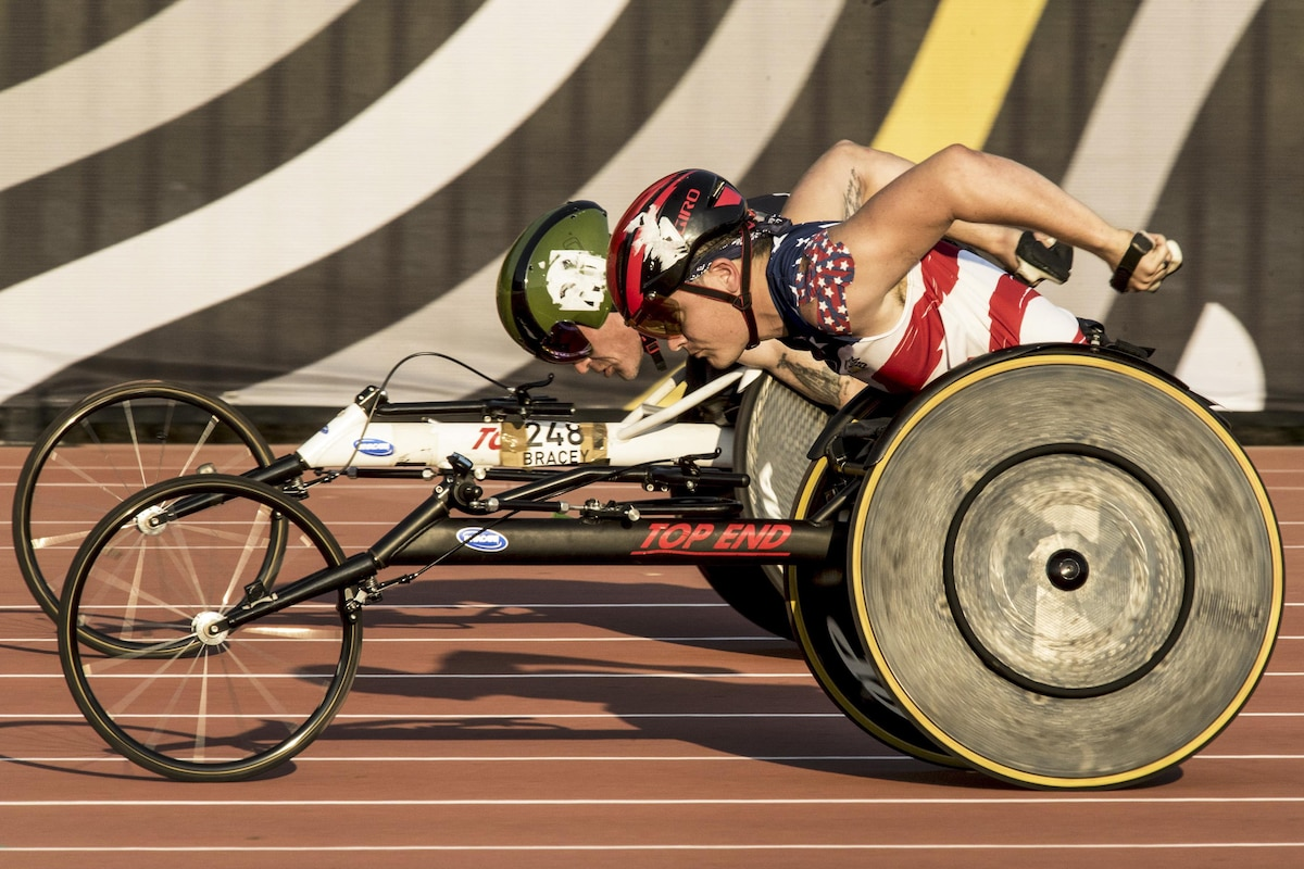 A Marine speeds past a British athlete in a wheelchair track event.