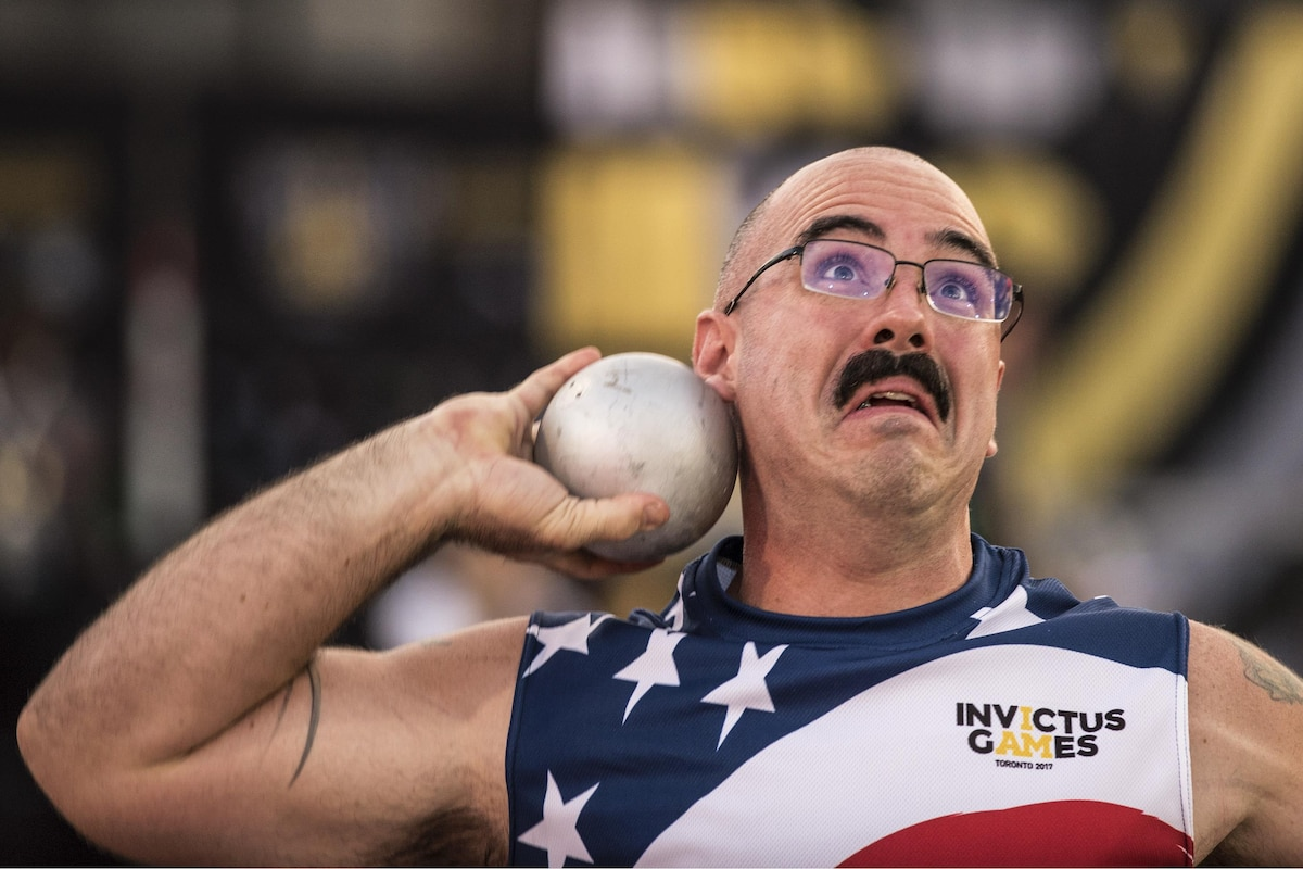 An airman makes a face as he prepares to throw a shot put.