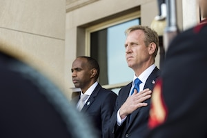 Deputy Defense Secretary Pat Shanahan holds his hand over his heart while standing with another official.