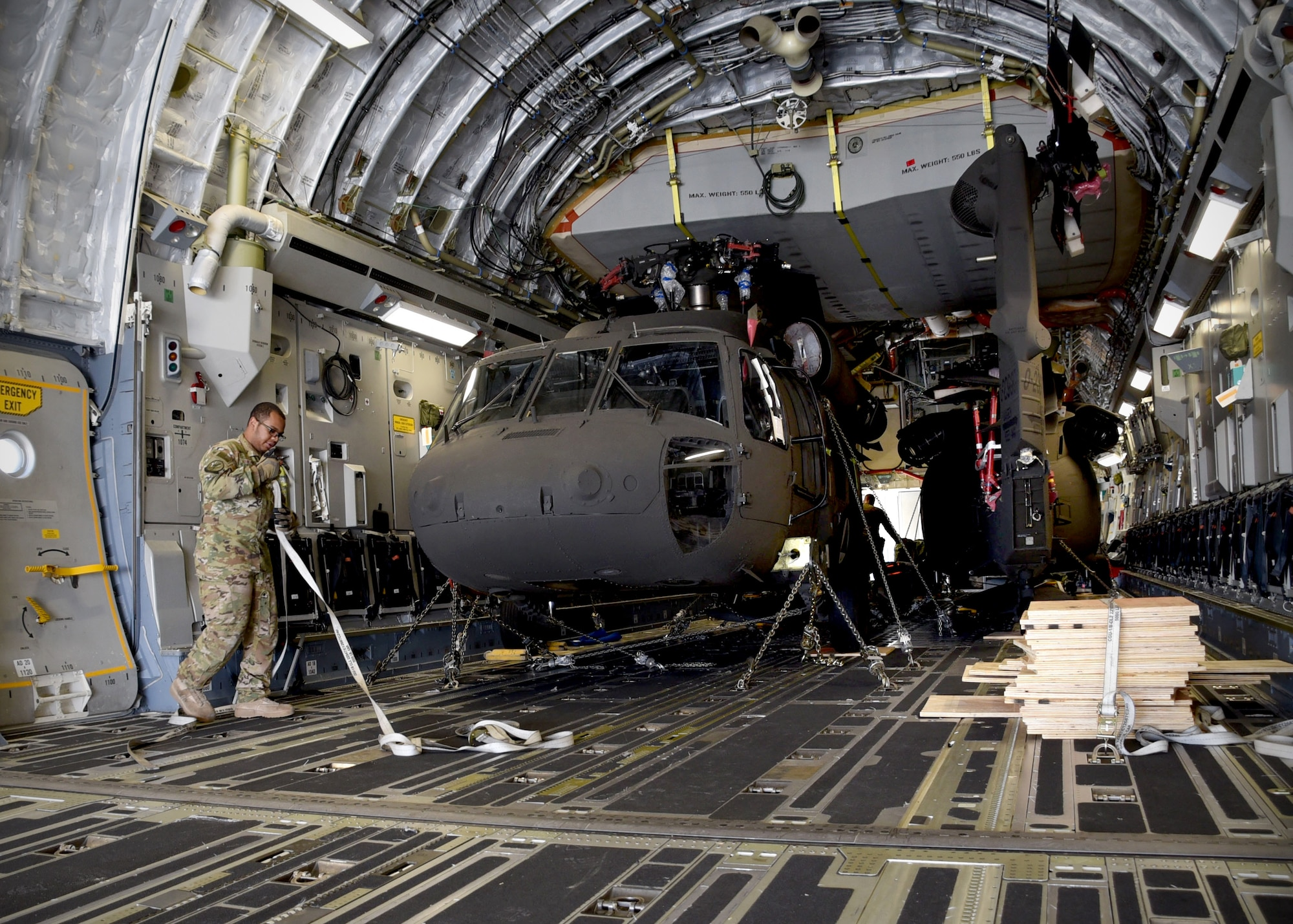 A U.S. Air Force C-17 loadmaster assigned to Charleston Air Force Base, S.C., prepares two Afghan Air Force UH-60 helicopters for unloading Sept. 18, 2017, at Kandahar Air Field, Afghanistan. These are the first UH-60s to be delivered to Afghanistan for the modernization of the AAF and development of a professional, capable and sustainable Afghan Air Force.